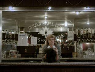 """A white person is standing behind a bar, having both elbows on the bar surface and cleaning a glass with a cloth. They are positioned in the centre of the image and are wearing a grey jumper over a white shirt. They look in thought. Behind them are alcohol bottles and a large mirror on which the words """"Ulster Maple Leaf Sports and Social Club"""" are written."""