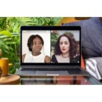 A picture of a laptop sat on a coffee table. On the laptop there are photos of two women. On the left is a black woman with her hair loosely tied up wearing a white top. On the right is a white woman with shoulder length brown curly hair wearing a black top.