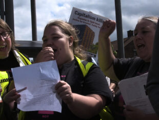 Three women stand next to each in a protest, left one with dark short hair and glasses, middle and right one with long blonde hair tied in a ponytail. The one in the left is holding a paper for the woman in the middle who is speaking through a megaphone. The woman in the right is screaming while holding her fist up and holding a bundle of papers. In the back a placard reads: Capitalism kills, Organise to fight back, Justice fro Grenfell, Safety for..
