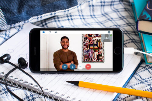 An mobile phone is sat on a notebook surrounded by books and pencils and a set of headphone. On the phone is a young black man with short hair and a beard, wearing a brown jumper. He is stood with his arms crossed, next to a brightly coloured piece of art on the wall.