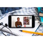 An mobile phone is sat on a notebook surounded by books and pencils and a set of headphone. On the phone is a young black man with short hair and a beard, wearing a brown jumper. He is stood with his arms crossed, next to a brightly coloured piece of art on the wall.