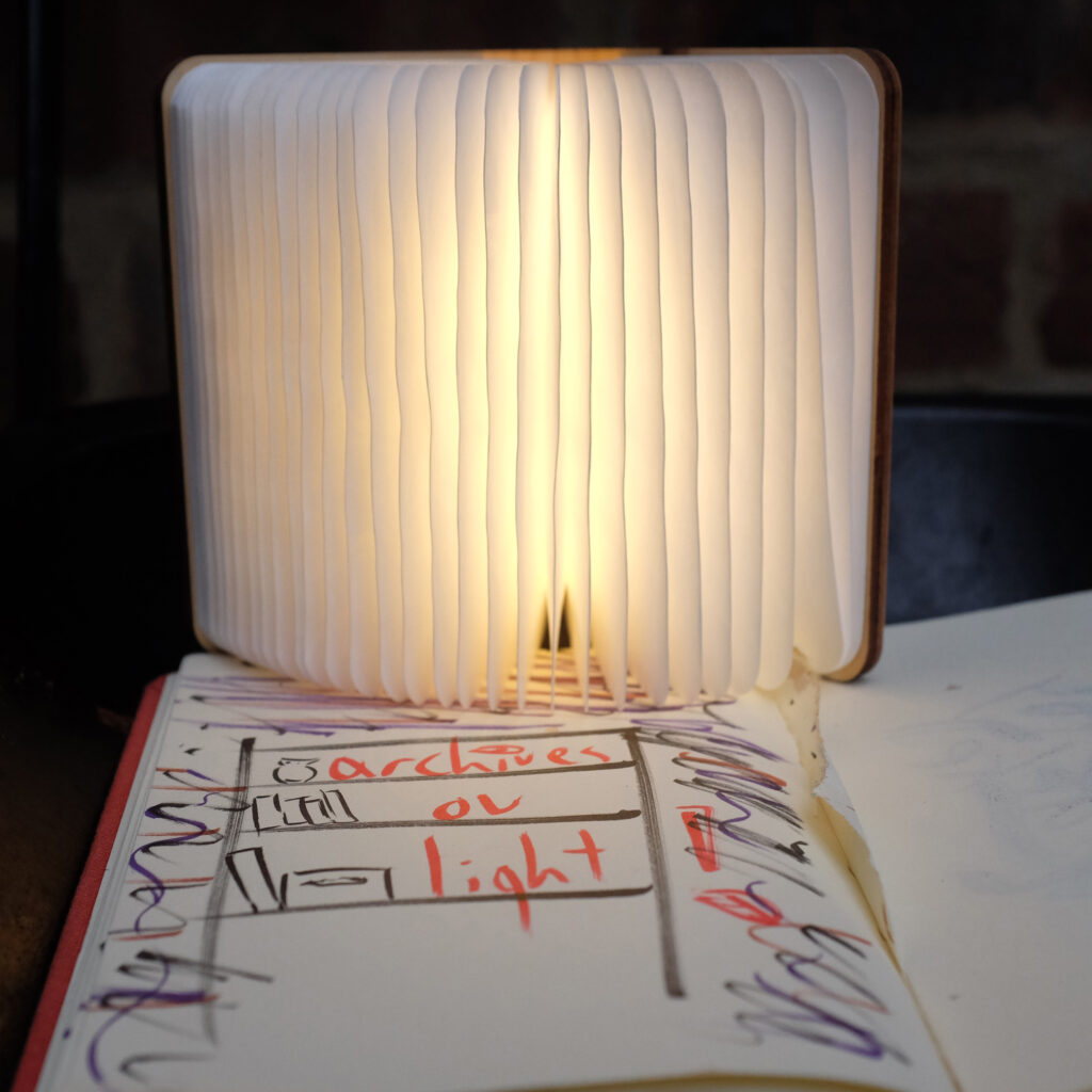 A photo of a lamp which looks like an open book sat upon an open notebook. Orange writing on the page reads: archives of light
