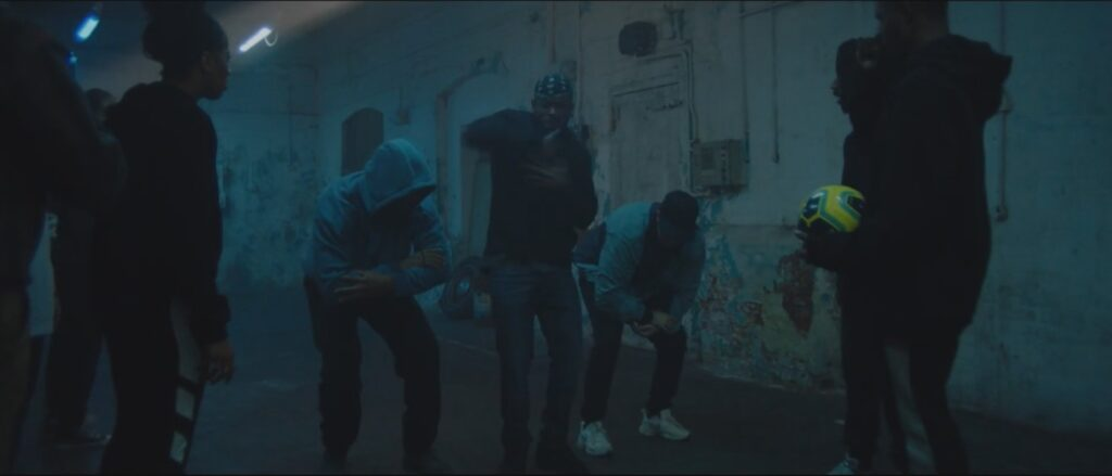 Film still showing a group of ethnically diverse young adults dancing in a warehouse