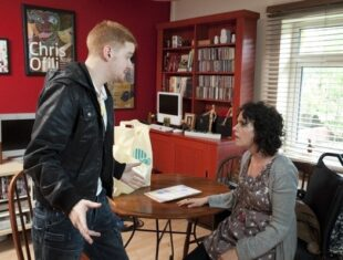 Film still of two white male and female actors in a indoors scene from the ITV soap