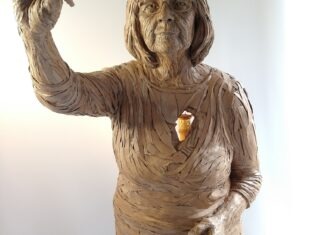 Life-size sculpture of an elderly white woman - seen from the front - holding a pen in the air.