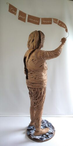 Life-size sculpture of an elderly white woman - seen from the side - standing against a white background