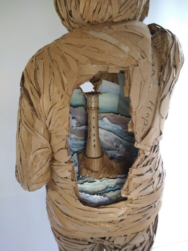 Life-size sculpture of an elderly white woman - seen from the back - exposing a lighthouse seen through a cavity inside the figure