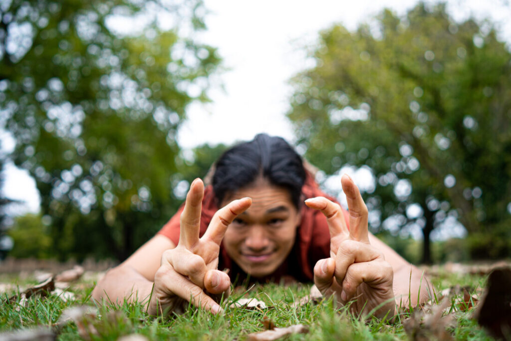 Man of east-Asian descent lying on some grass making a dancing motion with his fingers