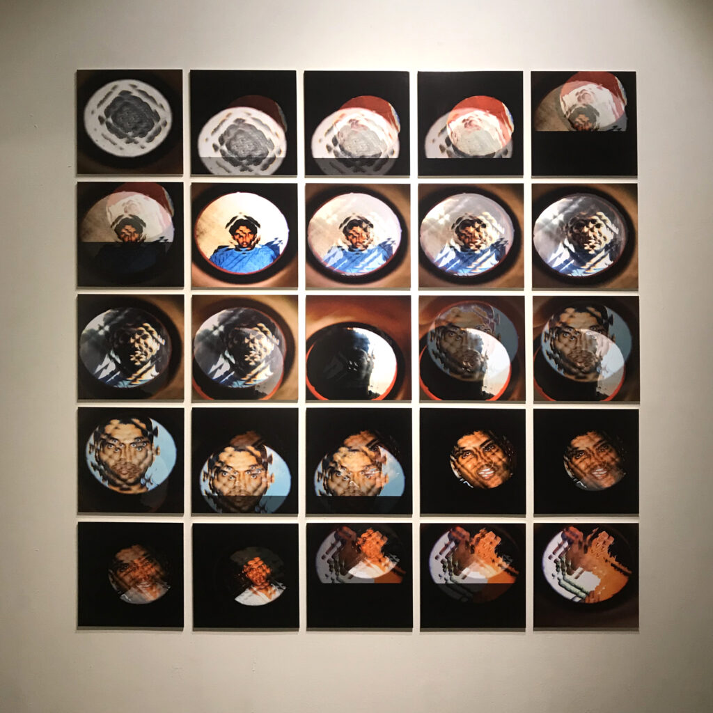 Artwork made up of 25 square photographs arranged ina large square. Each photograph shows a South Asian man shot through a kaleidoscope from different angles.