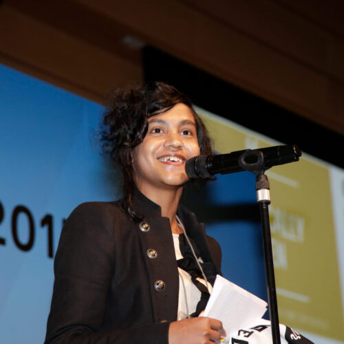 A young south Asian woman smiling as she speaks into a microphone