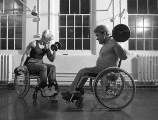 This is a black and white photograph of a white woman bodybuilder in her thirties or forties, and a white male body-builder of about the same age, who sit in their wheelchairs while working out. The woman has very defined muscles, shoulder length blond hair tied back in a ponytail, and is wearing a vest top, jogging bottoms and white trainers. She is using two dumbbells to work her biceps. The man is well built and has short dark blond hair. He is bare-chested, wearing trousers and black trainers, and is using a barbell to do a shoulder press. Behind them are large, tall windows and a radiator. The room looks like a school or institutional gymnasium. The walls are white and the floor is dark and smooth.