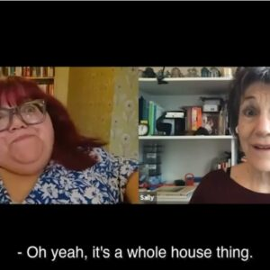 A disabled with woman with red hair and an older white woman with short black hair speaking on a Zoom call