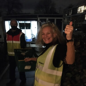 White woman in high viz jacket and white tesco delivery man holding either end of a green crate