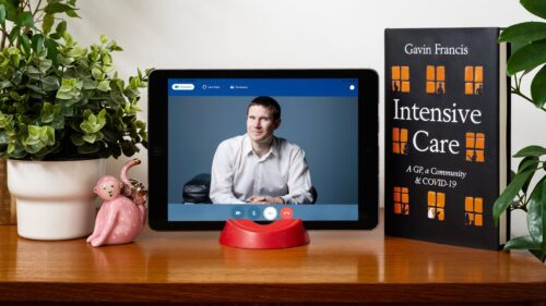 Dr Gavin Francis appears on an ipad, which is propped up on a brown table. To the left of the ipad there's a plant and a small monkey statuette. To the right is the book Intensive Care.