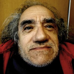 Close up shot of Nabil Shaban Jordanian-British man in his 60s with stubble and greying hair