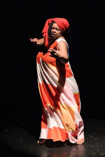 photo of a black woman full-length dressed in a bright, flowing orange and white dress. She wears a bright orange headress on her head