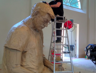 A white man dressed in black up a ladder adding to an oversized self-portrait sculpture made out of cardboard in a large empty room
