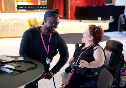 A woman sat in a wheelchair laughing in conversation with a man who is smiling. They are sat next to a table with a laptop, pamphlet and mobile phone on top.