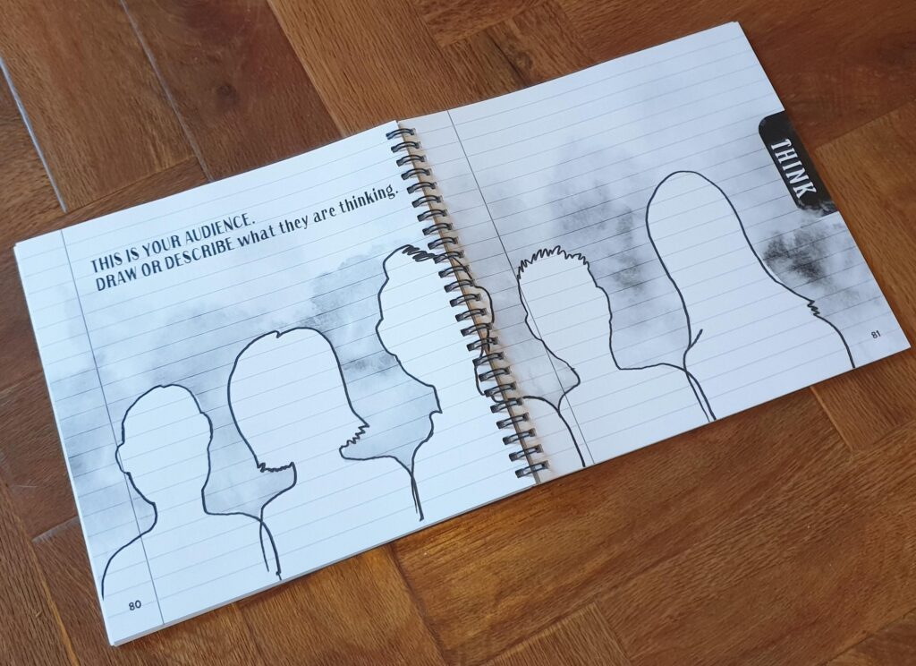 Photo of an open book with line drawings of figures across two pages