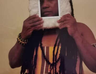 A black person with long braided hair looks through a feathered photo frame. They are wearing a striped shirt.