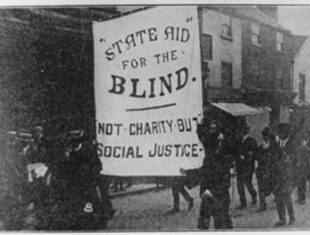 A black and white photograph of protesters carrying a large banner which reads 'Not charity but social justice'