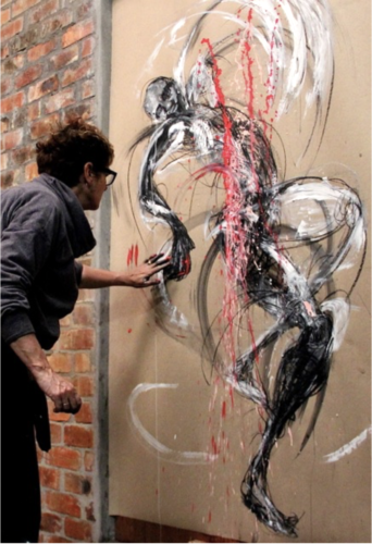 photo of white female artist painting a dynamic figure on a large canvas