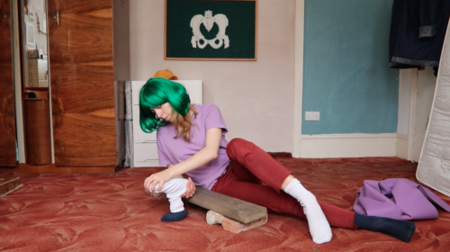 Performer Alice Gale-Feeny is in motion with objects including a sock, some bricks and a plank of wood. She is wearing a bright green wig and is performing in a domestic space.