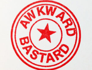 Logo for Awkward Bastards in the style of a rubber stamp in red. There are two concentric circles with the words Awkward Bastards within and a red star at the centre of the stamp.