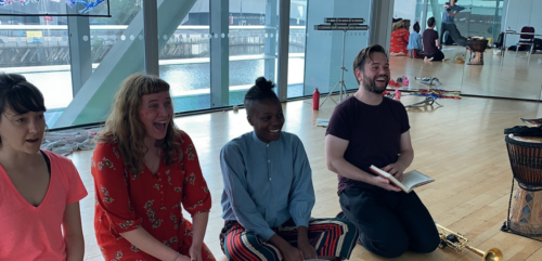 Four people sit on the floor in a studio.