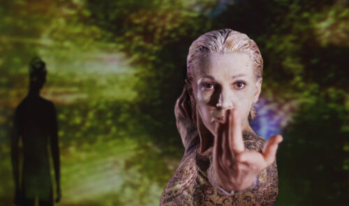 A dancer stares down the lens of the camera with her arm outstretched, her pointer finger pointing at the camera. Her face and hair are powdered white and her hair is slicked back. In the background are abstract lime green, yellow and black shapes, as well as a shadowy figure.
