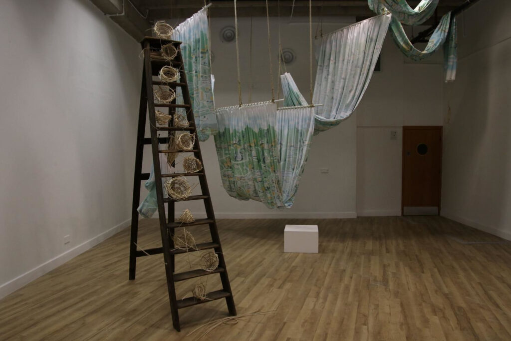 Exhibition shot showing ladders stacked with half woven baskets and draped material hanging from the ceiling
