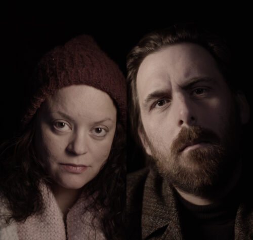 Film still portraying a white male and female, looking directly at the camera