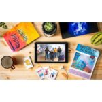 Four people from Heart n Soul appear on the screen of a tablet. The tablet lays on a wooden table. Around the tablet are an orange and yellow painting; some playing cards; Inclusive Futures poster; a blue, black and white artwork, and a succulent plant.