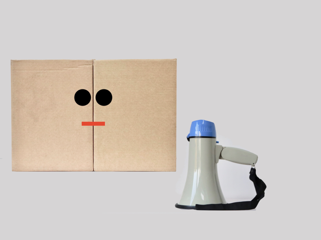 Cardboard box with eyes and a mouth. A megaphone is placed next to it.