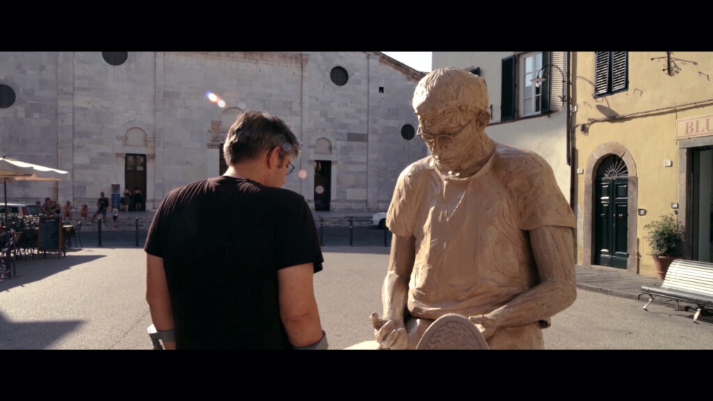 Still image of the artist sitting with back to camera, next to a life size sculpture