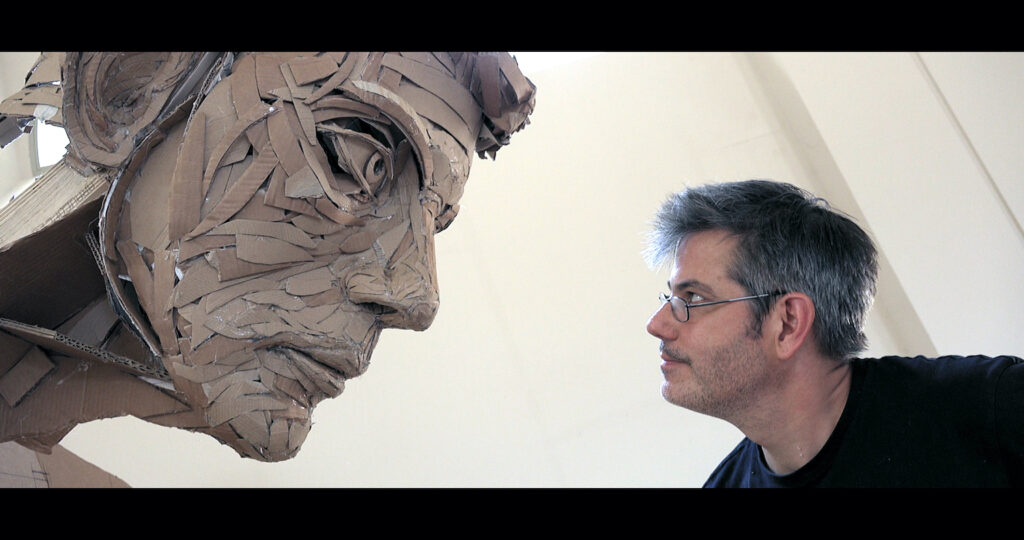 Still image of a white male artist in a studio profiled with the face of a large sculpture, he is working on