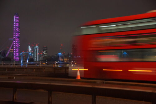 A blurred photograph of a red bus in motion passing the London eye on a bridge at night