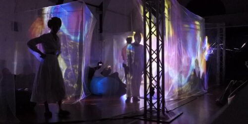Figures stand in a darkened room, surrounded by translucent gauze screens lit by colourful, abstracted projections