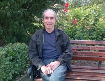 An older man with grey receding hair sits on a bench in a garden. They are wearing a dark denim jacket, a navy blue t-shirt and lighter blue jeans.