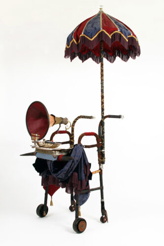 A walker dressed up with a red and blue fringed parasol, draped tapestries, a silver platter, a gramophone horn and cow horns.