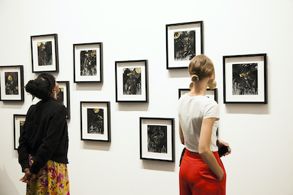 Two people stand looking at art on the walls of a gallery.