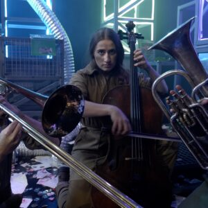 3 actors in brown jumpsuits set within a futuristic stage set play instruments: trombone, tuba and cello