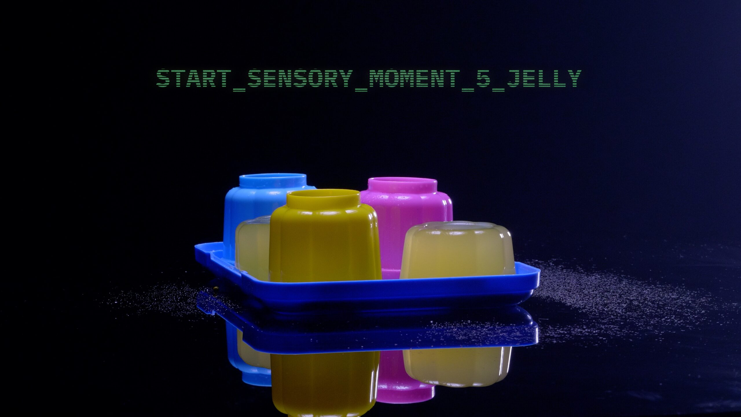 FOur colourful jelly moulds on a plastic tray in front of sci fi text which reads start sensory moment 5, Jelly