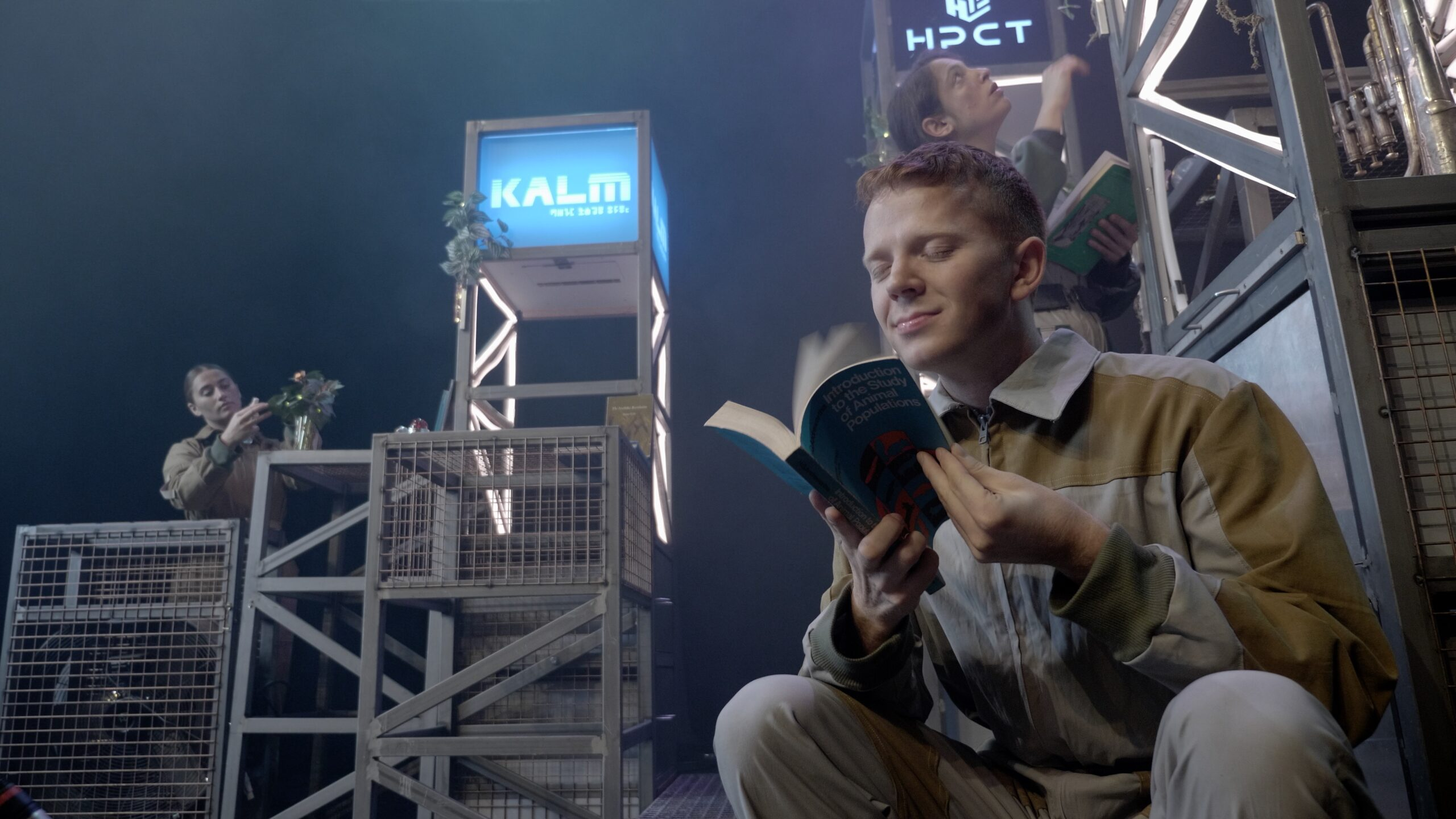 3 white actors in space jumpsuits in a futuristic stage set, one of them is reading a book while the other two scour scaffolds looking for objects