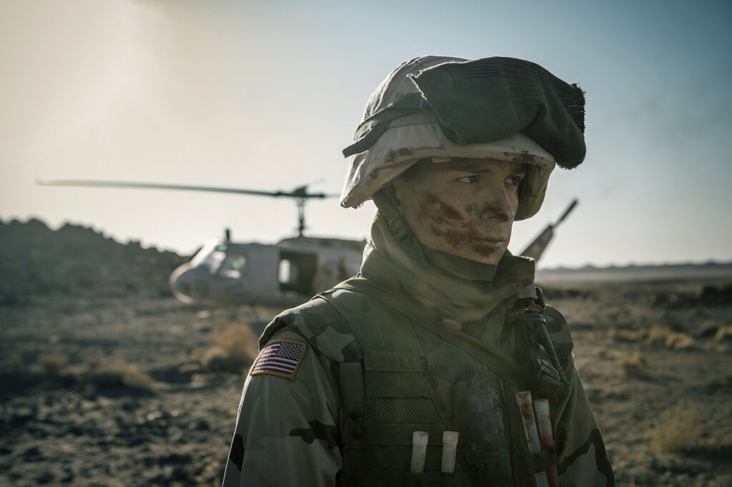 Photo of a white, male soldier in uniform with a helicopter behind him