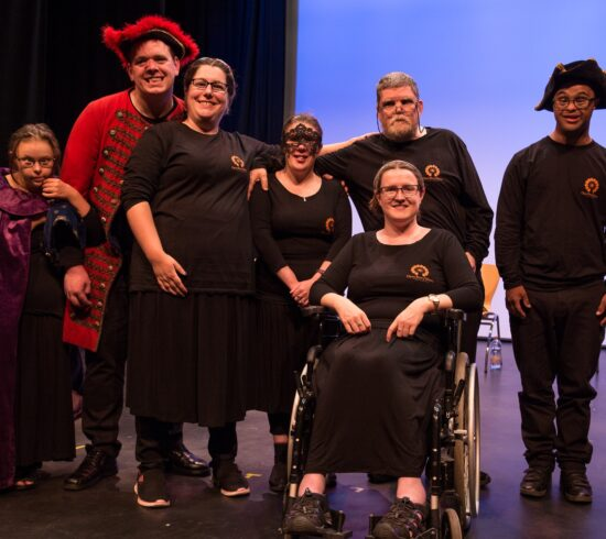 Cast members of the OpenStoryTellers smiling at the camera on stage at the Merlin Theatre