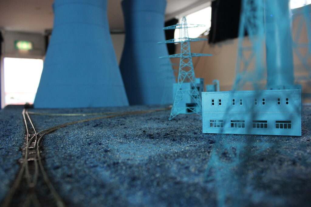 Photograph sculpute depicting a power station using modelling equipment, it's all painted blue