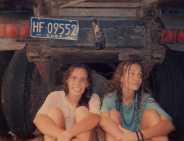 An old analogue color photo of Heidi Hassan, on the right looking at the camera and smIling, and Patricia Perez, on the left looking up, in their teens, seated on the floor. Behind them a truck with a plaque that reads: HF09552- Cuba.