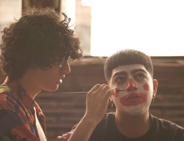 A colour image of two teenagers, the one in the left with short dark curly hair and glasses, is painting the face of the one in the right as a clown, with red paint in the lips and nose and white paint in the rest of the face.
