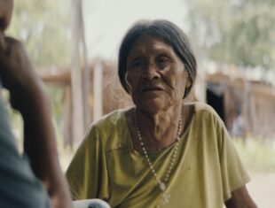 A colour image of an Ayoreo indigenous person with long grey hair tied back a light pastel green t.shirt and a white rosary necklace. The person is looking at someone else in front who is almost out of frame and out of focus. In the background there is a house and greenery landscape out of focus.